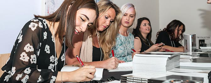 Public Relations — Corporate Communications students  sign books for guests at the launch