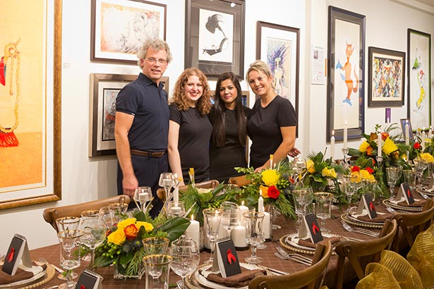Four people take pose behind the decorated tables